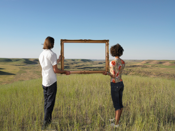 man-and-woman-holding-frame-in-open-field